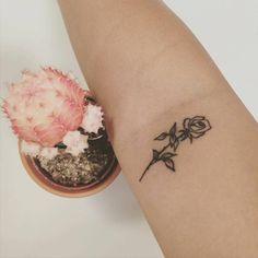Rose tattoo on Madeline's bicep. Tattoo artist: Kat Jones