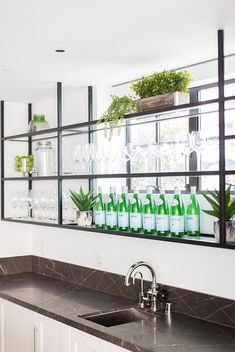 Chic basement bar features black metal shelves fixed in front of a window and ab. Chic basement bar features black metal shelves fixed in front of a window and above white shaker ca Glass Bar Shelves, Metal Kitchen Shelves, Glass Shelves In Bathroom, Custom Kitchen Cabinets, Metal Cabinets, Wall Shelves, Rustic Basement Bar, Basement Bar Designs, Industrial Basement