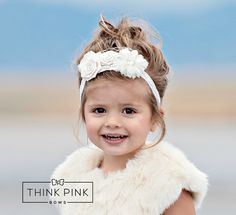 """If you're looking for asimple and sweet timeless look, you've come to the right place. Our """"Simple Sweetness"""" Flower Headband is the perfect combination of everything feminine for your little girl to wear. The headband consists of beautifulwhite flowers in varying sizes and textures. Each Flower is embellished with gorgeousfaux pearls and rhinestones. The nettingveil material adds the final touch, giving this beautiful piece a sweet andfemininevintage look.The flowers are backed…"""