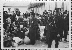Slovakia, Jews with their belongings, awaiting deportation. On the side stands an armed man of the Slovakian militia.