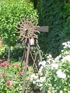 RUSTIC Utah Item # 26: Decorative windmill for use as yard art. Legs make great trellis for climbing plants. Head made from antique rotary hoe wheel.