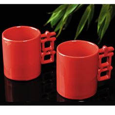 "Drink to Double Happiness. What could be better than a doubly auspicious start (or middle, or end) to your day? These Double Happiness Mugs are red, the Chinese color for happiness and the handles are the Chinese character for happiness. Place the mugs handle to handle and you create double happiness. Ceramic. Dishwasher and microwave safe.  				  				 3.8""h x 3.15"" dia., exclusive of handles. Set of 2."