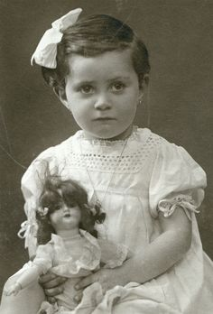 Sweet antique photo of a little girl and her dolll, circa 1900.