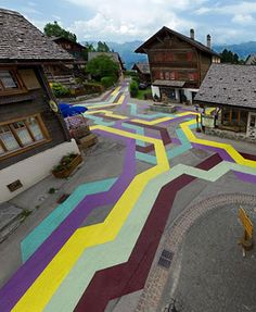"""Sabina Lang and Daniel Baumann are a pair of Swiss artists who have formed a """"multidisciplinary studio"""" to create a variety of bold and playful public art installations. In the typical Swiss ski town of Vercorin, Lang Baumann transformed an intersection into """"Street Painting #5."""" The 100 by 60 meter art piece was created using """"road marking paint."""""""