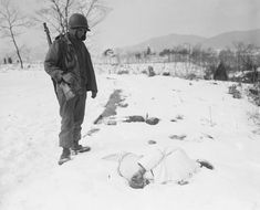 Cpl. Clifford Rodgers, Muskogee, Okla., looks at bound wrist of a Korean Civilians found in deep snow on Jan. 27, 1951 near Yangji, about 15 miles northwest of Ichon on the central front. The atrocity victim, one of several found in the area, presumably had been killed by reds retreating before allied advance. (AP Photo/Max Desfor