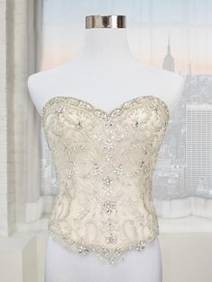 (IV3196) *Bridal Separates* strapless net beaded bridal corset top is perfect for the bride seeking a one-of-a-kind look for her wedding day. Designed to pair easily with any of the separate skirts in the Simply Val Stefani bridal collection, this corset top can be worn with a ball gown skirt, paired with an A-line silhouette, or teamed with a trumpet style in order to create a variety of chic and elegant looks. Available in gold, ivory, and white.