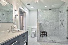 Prepossessing White Carrera Decorating Ideas in Bathroom Traditional design ideas with Prepossessing Carrara marble chandelier doorway glass shower gray herringbone mirror rain showerhead sink