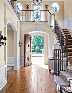 Beautiful Entry..i like the stairs going the opposite direction of most, with a small walkway over the door. still keeps the two-story foyer (with window) feel!