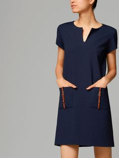 simple navy dress with pockets and brown leather