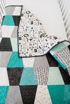 This monochromatic tumbler baby quilt is one of my absolute favorites. The newborn quilt is done mostly in black, whites, and grays, but then has beautiful pops of mint and teal. This baby quilt would look adorable in a Scandinavian style nursery or a minimalistic style nursery. Its