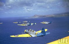 Douglas TBD-1 Devastators of Torpedo Squadron Six in battle fleet exercises operating from the USS Enterprise are seen off the coast of Oahu (ca. early 1941). The back of the extinct Diamond Head volcano is visible at the shoreline in the background.