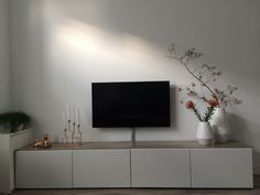 - Tv meubel van ikea zorgt voor veel opberg ruimte en is in dezelfde hoogglans wit als de keuken. Op het meubel ligt hetzelfde laminaat als op de vloer waardoor het geheel rustig blijft. De rode tak en bloemen geven een mooi contrast tegen al het wit.