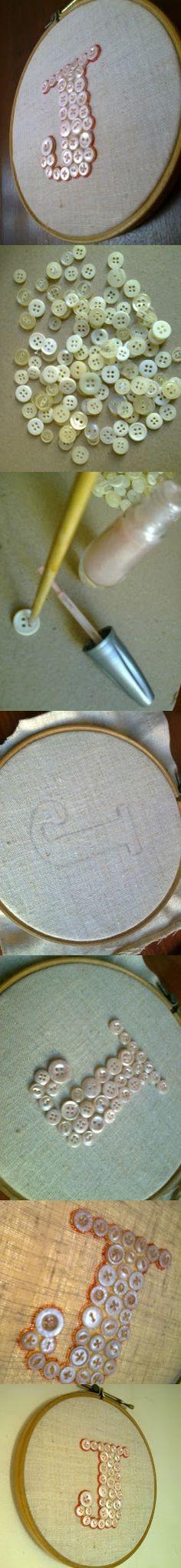 Jud, do Blog JUD artes: Tantos botões sem graça em casa, de antigas camisas masculinas, pintei com esmalte para unhas, um rosinha cintilante.  Transferi o risco da letra para um pedaço de  linho.  Posicionei os botões mais ou menos dentro do contorno da letra, fixei com um pinguinho de cola um a um para costurar depois.  O tecido estiquei bem no bastidor, cortei a sobra no verso e passei cola no recorte para não desfiar.  Com caneta permanente vermelha risquei todo o contorno dos botões.