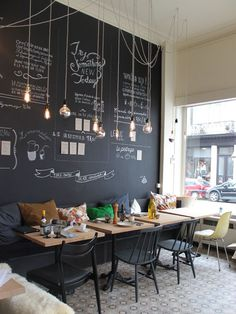 Modern and cheerful coffee shop decor with a chalkboard wa .- Modernen und fröhlichen Coffee-Shop Dekor mit einer Tafel Wand und hängenden G… Modern and cheerful coffee shop decor with a blackboard wall and hanging light bulbs - Coffee Shop Design, Design Shop, Cute Coffee Shop, Small Coffee Shop, Cozy Coffee, Leo Coffee, Coffee Cup Reading, Bistro Design, Lounge Design