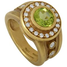 Kieselstein-Cord Peridot Diamond Yellow Gold Ring. Beautifully designed and made of the finest materials, this gemstone ring from Kieselstein-Cord is absolutely divine! The ring is made of 18K yellow and boasts shanks and a bezel set with diamonds. Lastly, a single ~5.40ct peridot main stone adds a hint of color to the overall design. Circa 20th century.