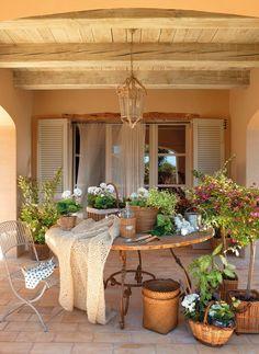 El porche  Mesa redonda de The Masia Store. Lámpara de techo, en Otranto y plantas de Jardiland.