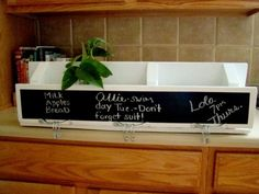 kitchen organizer made of a pallet, some drawer pulls and hooks. painted with chalkboard paint.