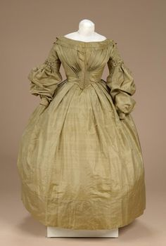 1830s Dress w/bateau neck, dress fastens in back w/hooks & eyes from neck to waist; 2 diagonal rows of buttons applied to back of dress which follow line of pelerine when attached; lined with glazed linen.  Pelerine, same color & fabric as dress; 2 rows of ruching trim the edge matching those at top of sleeve of dress; a row of fabric covered buttons is applied at shoulder seam. LitchfieldHisSoc, CT.