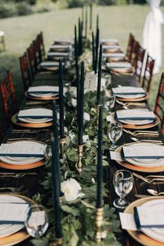 christy cassano; christy cassano-meyers; winter wedding; oregon wedding; forest wedding; fashion inspired wedding; reception in forest under white tent; bare wooden tables; wooden tiffany chairs with white cushions; hanging greenery; white curtains; black candles; brass candlesticks; white green floral garlands; gold plates; gold cutlery;