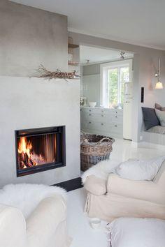Un salon qui nous acceuille à bras ouverts, parfait pour l'hiver avec ses fauteuils confortables, sa cheminée et ses couleurs claires pour compenser les journées plus courtes.   White and cozy Scandinavian home - 79 Ideas