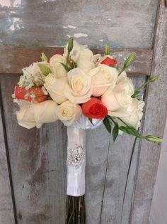 Bouquet de rosas vendela y coral, con detalle de broche plata.