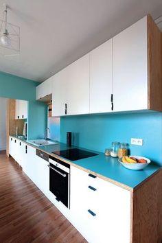 """Cuisine très sympa : """"Le plan de travail et les rangements associent modules standard (""""Rationell"""", Ikea) et habillage sur mesure. Les poignées de porte sont des bandes de cuir fixées à l'intérieur des placards. La gamme couleur, mise au point par la propriétaire avec l'aide des architectes, donne son unité à l'appartement : une palette de bleus (céladon, bleu canard, bleu """"Air France""""), déclinée sur le plan de travail en stratifié, la crédence ou l'arche de séparation cuisine-séjour."""""""
