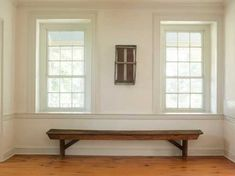 Beneath unadorned windows in the front room, a Shaker bench emphasizes the low dado and strong architectural lines.