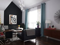 The black accent wall shows off the architecture and ceiling height in this 1950's house via Design*Sponge.