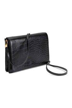 Schoudertasje: Een schoudertasje van generfd imitatieleer met een klep met een magneetsluiting, een smalle, afneembare schouderriem en twee vakken. Gevoerd. Afmetingen 4x15x21,5 cm.