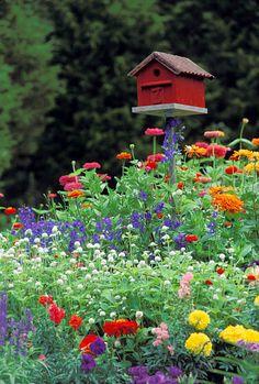 Red barn birdhouse in brightly blooming summer flower garden