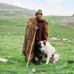 Portrait of shepherd wearing sheepskin cloak, wearing green hat, holding stick standing with sheepdog against background of Urdele Pass, Carpathian Mountains, July Historical Clothing, Historical Photos, Carpathian Mountains, Green Hats, Folk Costume, People Of The World, Eastern Europe, Cloak, Traditional Outfits