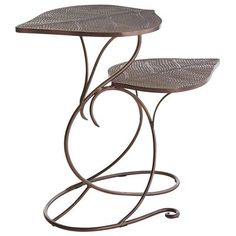 """Everything old is <i>nouveau</i> again—more specifically, our spectacular Art Nouveau-inspired Leaf Accent Table. Handcrafted from iron, each piece is a tribute to turn-of-the-20th-century decorative arts, including such details as serpentine """"stems"""" and engraved, granulated metal. Better yet, its twin-leaf design means you're getting two tables in one."""