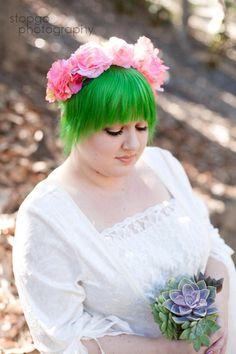 Noiva com cabelos verdes e coroa de flores rosa.