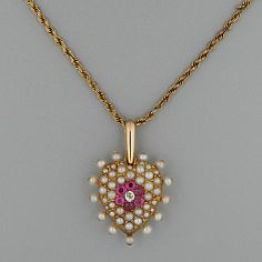 A late Victorian heart-shaped pendant Pavé-set with an old-cut diamond bordered by rubies within a half pearl mount, bordered by pearls, on chain, 2.0 x 2.0cm.