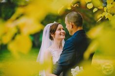 Bride & groom through autumn leaves