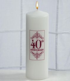 """40th Wedding Anniversary Candle made of solid white wax. It features a classic cylindrical shape with a tapered top. The front of the candle is printed in red with a rectangular emblem. Inside the emblem it is printed with two flourish borders and the phrase """"40th Anniversary""""."""