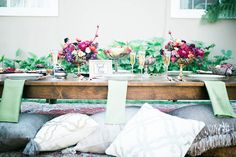 Lush tablescape with fresh fruit, jewel-tone floral centerpieces and a lovely pillow filled seating area over the Persian rug is unique and exotic treat for a bridal shower.