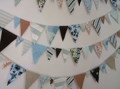 "Throw an awesome party, gussy up a bedroom, or drape it around your window- this fabric bunting will look fantastic wherever you put it!     The bunting is 20 feet long and is composed of three sizes of fabric triangles, ranging from 1 1/2"" wide to 3 1/2"" wide. The triangles are attached with a running stitch along the top and the bunting is double sided.     The Seaside Palette is a lovely combination of robin's egg blue, chocolate brown, tan, and white.     Would you like a fabric bunting…"