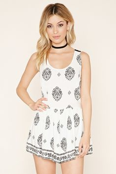 Covered in an ornate print, this sleeveless woven romper features contrast crisscross-back straps, a round neckline, gathered waist, on-seam side pockets, and an invisible zipper at the side.