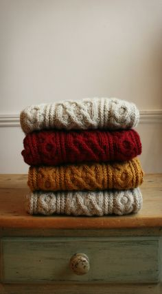 pile of chunky knit sweaters