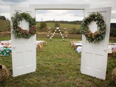 Welcome guests to an outdoor ceremony with a special entrance by setting up a frame with wreath-decked doors. At the aisle's end, simple wooden ladders create a unique altar adorned with flower bouquets and garland.