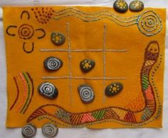 "Teach kids aboriginal art symbols, and have kids paint aboriginal art symbols on a set of stones to use to play tic tac toe (also called ""ngaka ngaka"", which means ""look look"")."