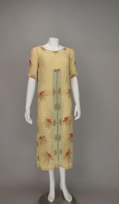 House of Adair, France - beaded yellow cotton dress from the 1920s, Venetian glass beads in floral patterns highlighted by geometric grids of white glass beads...pull on style dress is straight with inverted pleats, which are lined in pale green, at front and sides...round neckline, elbow length sleeves with an inner gros grain waist band. Front 2