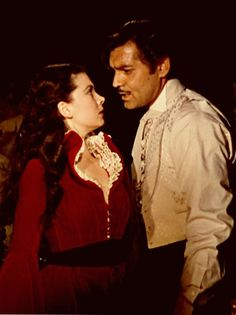 Vivien Leigh & Clark Gable.  Rhett drops his cool indifference.  He passionately presses Scarlett against his body.  He will claim her as his own tonight.
