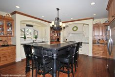 Black Kitchen Island with Butcher Block and hanging basket storage. Brown cabinets with Double door Fridge and Freezer in Stainless Steel Wood Floors Cream cabinets by sink. 6 different woods in one Kitchen. chandelier pot rack Glass upper Cabinets Tile Back splash