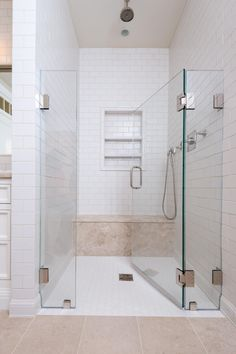 This bathroom suite features and walk-in shower with built in bench and shelving, a top-mounted shower head and a hand-held shower head. In typical transitional style, it uses a variety of materials to mix textures in neutral colors for the calm feel without a boring look.