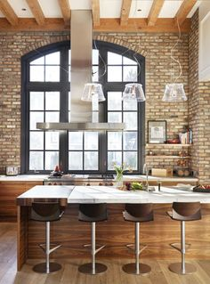 Bold, iron-framed windows (I love the curved top, and the huge scale of this window), exposed wooden beams, brick-faced walls, open shelving, steel fan, lots of large scale... all spell 'warehouse industrial'.