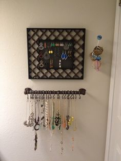 My new jewelry center. Necklaces are hanging on a towel rod with shower curtain holders. earrings are on a picture frame with needle art canvas replacing the glass. Bracelets and watches are on a hook from world market.