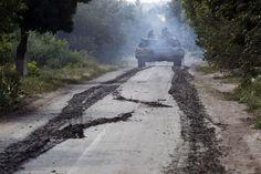 A Ukrainian tank moves along a road near Eastern Ukrainian village of Novoselivka Persha on July 31, 2014. (Reuters/Valentyn Ogirenko)