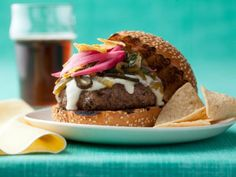 Throwdown's Green Chile Cheeseburgers : Bobby starts out with a simple burger patty but layers on the flavor with homemade toppings: queso sauce, roasted peppers and pickled red onions.